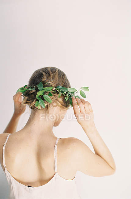 Woman fixing floral hair decoration — Stock Photo