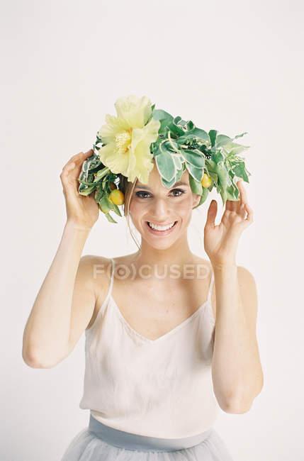Женщина регулирует цветочную корону — стоковое фото