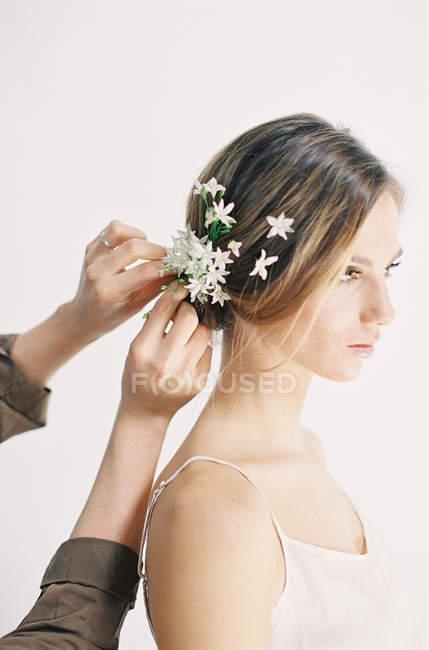 Stylistin verziert Haare mit Blumen — Stockfoto