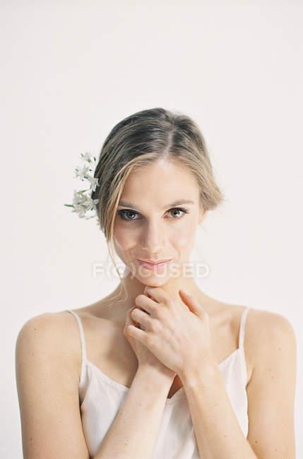 Mujer con flores blancas en el pelo - foto de stock