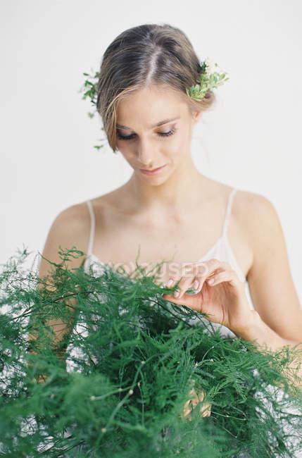 Mulher segurando folhas de samambaia decorativas — Fotografia de Stock