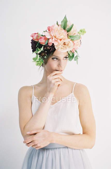 Жінка в квітка корони кусатися пальця — стокове фото