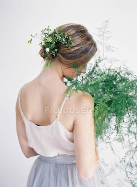 Frau hält Farnblätter in der Hand — Stockfoto