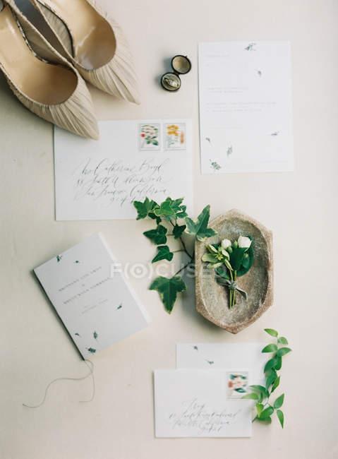 Bridal high-heeled shoes and wedding invitation — Stock Photo