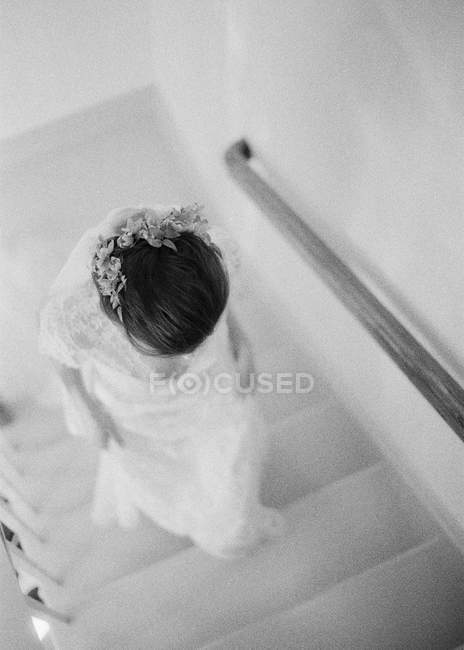 Женщина в свадебном платье поднимается по лестнице — стоковое фото