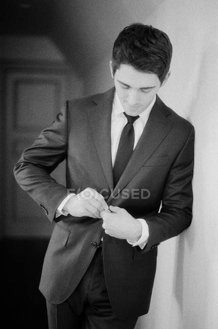 Young man doing up suit and looking away — Stock Photo