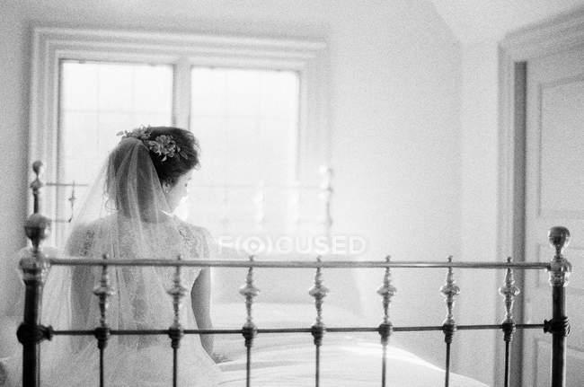 Frau im Hochzeitskleid sitzt auf Bett — Stockfoto
