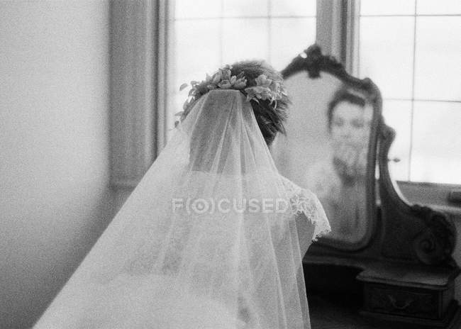 Woman in wedding dress looking at mirror — Stock Photo