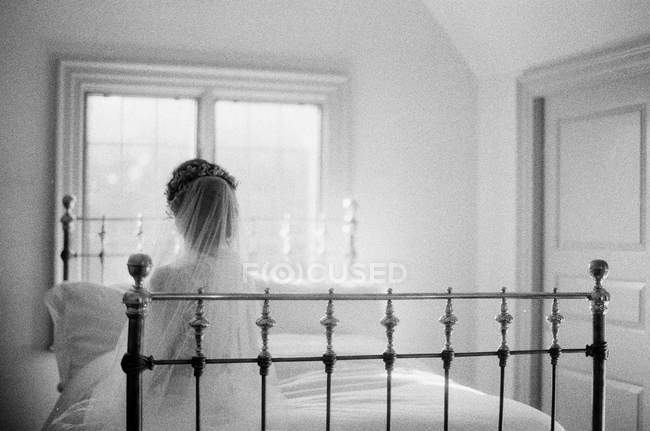 Woman in wedding dress sitting on bed — Stock Photo