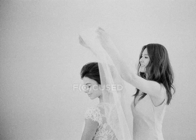 Mujer ayudando novia con velo - foto de stock