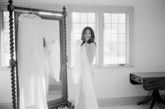 Woman in wedding dress holding vail — Stock Photo