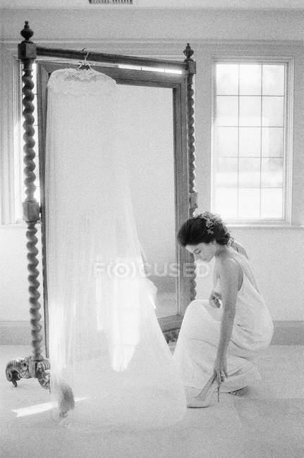 Donna in abito da sposa raccogliendo scarpe — Foto stock