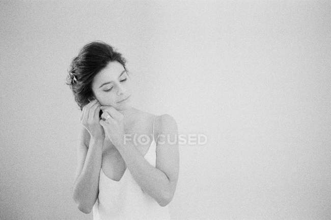 Woman in boudoir fixing earring — Stock Photo