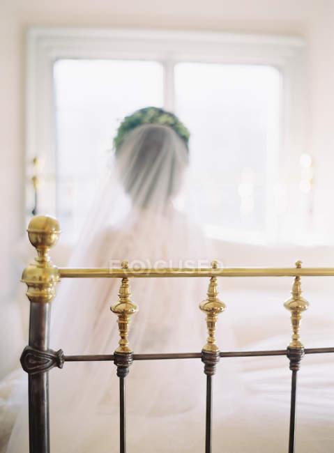 Frauen im Hochzeitskleid sitzen auf dem Bett — Stockfoto
