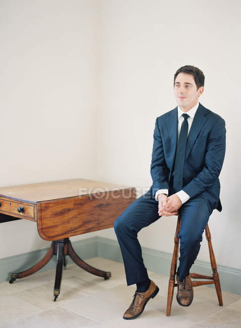 Man in suit sitting on chair — Stock Photo