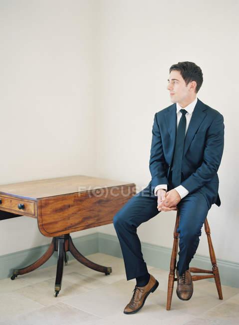 Людина в костюмі, сидячи на стільці — стокове фото