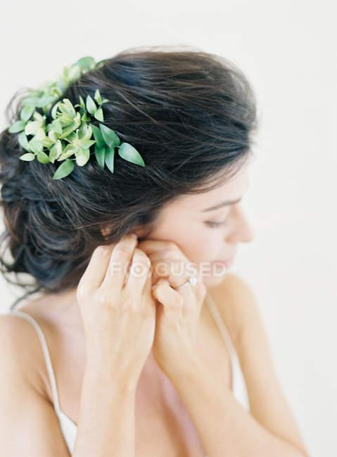 Frau fixiert Ohrring — Stockfoto