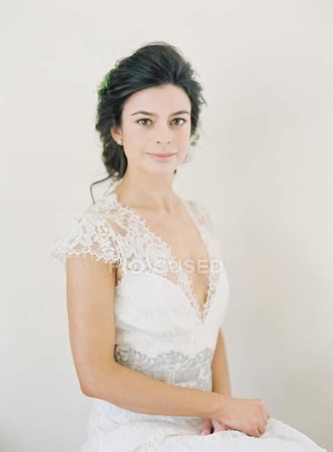Frau im Hochzeitskleid blickt in die Kamera — Stockfoto
