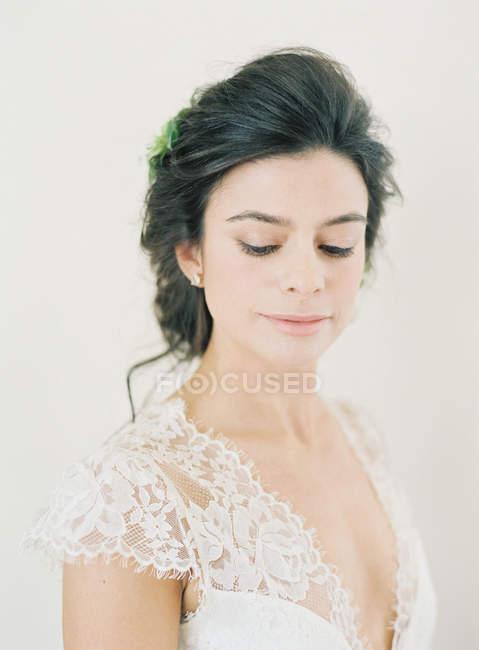 Donna in abito da sposa guardando giù — Foto stock