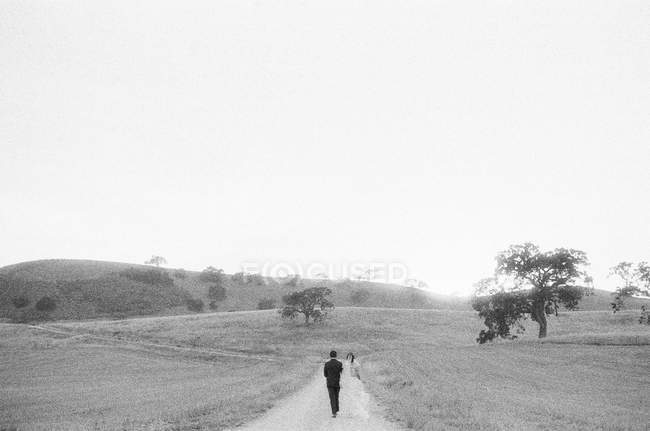 Newly wed couple walking in field — Stock Photo