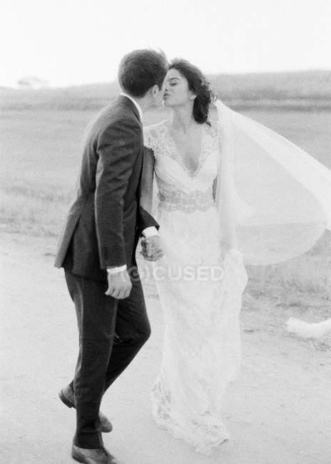 Пара держащихся за руки и идущих по полю — стоковое фото