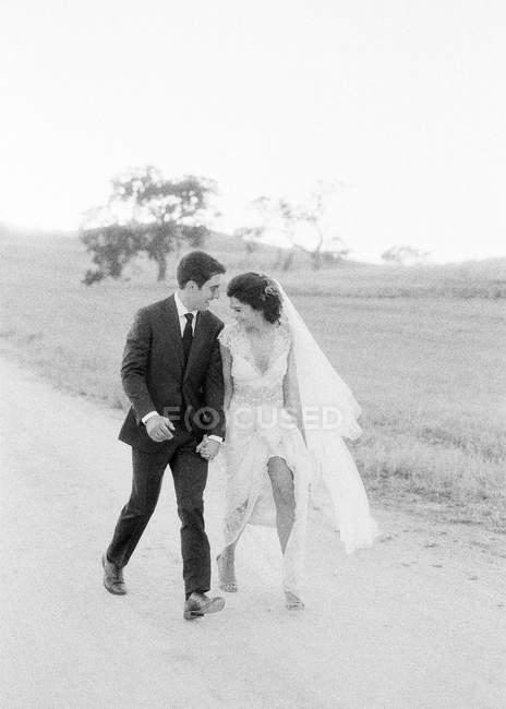 Молодая супружеская пара, гуляющая в поле — стоковое фото