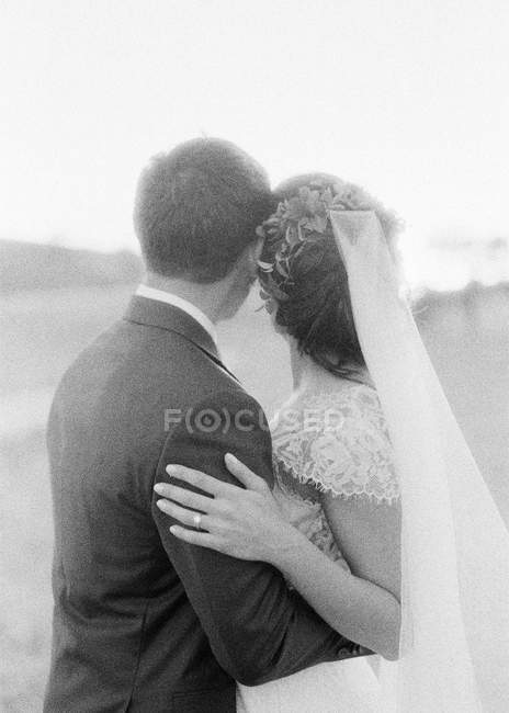 Couple in wedding attire hugging outdoors — Stock Photo