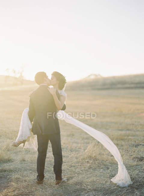 Жених держит и целует невесту — стоковое фото