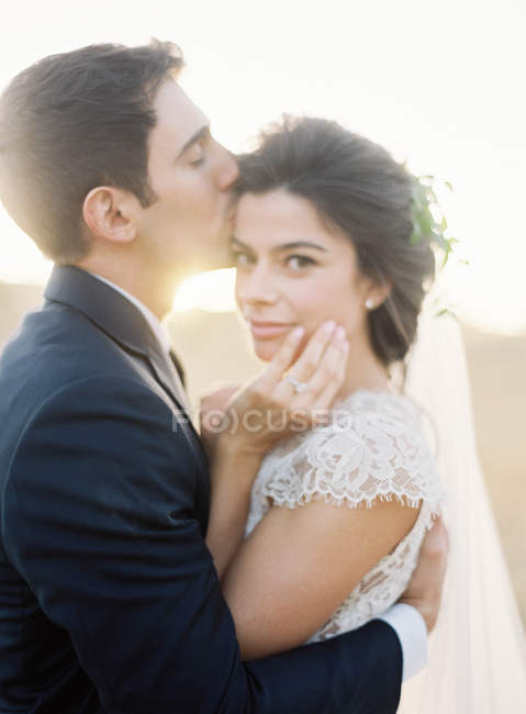 Groom gently kissing bride — Stock Photo