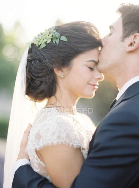 Groom gently kissing bride — Stock Photo