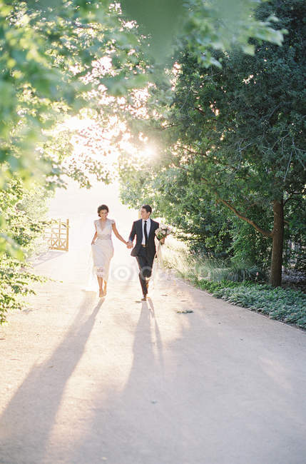 Newlyweds walking on rural trail — Stock Photo
