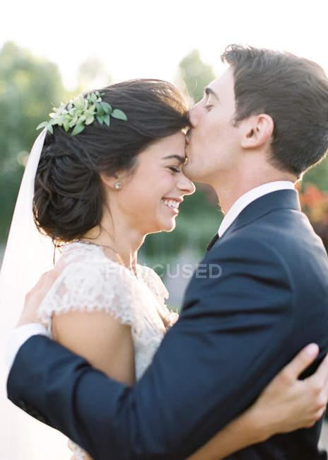 Groom hugging and kissing bride — Stock Photo