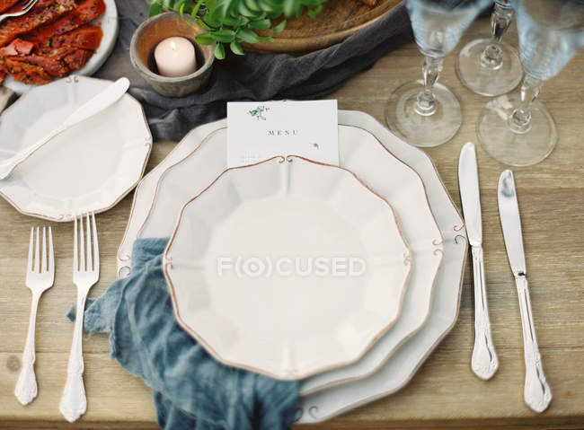Dinner table with porcelain plates — Stock Photo