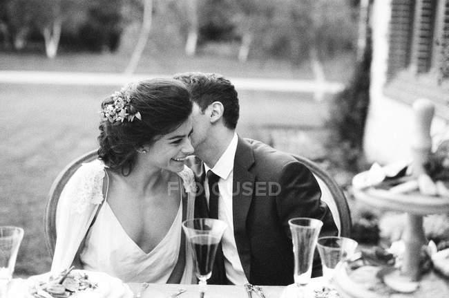 Groom whispering at bride ear — Stock Photo