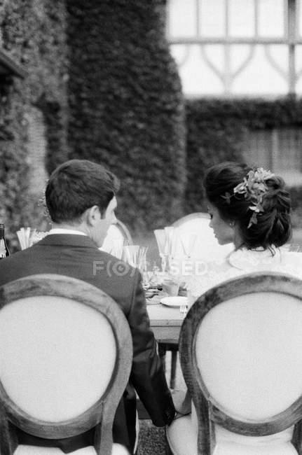 Marié et mariée assis à table — Photo de stock