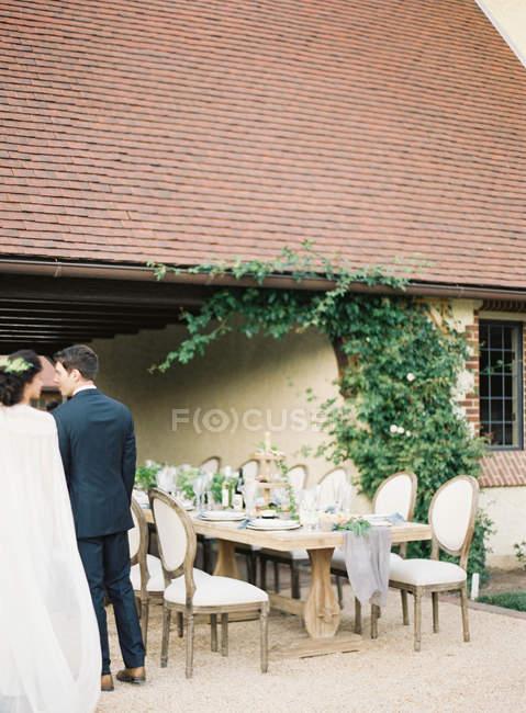 Le marié et la mariée debout à côté de la table du dîner — Photo de stock