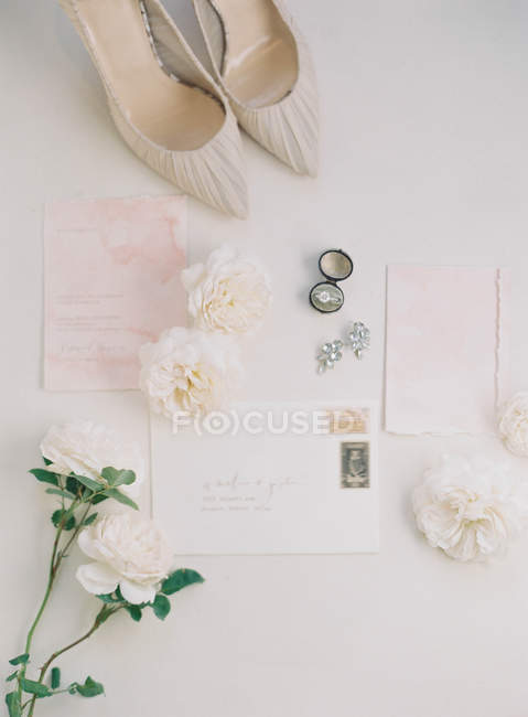 Bridal high-heeled shoes and invitation cards — Stock Photo