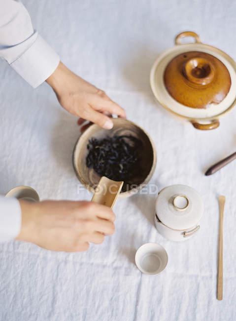 Mains ajoutant des feuilles de thé dans la théière — Photo de stock