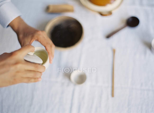 Hand pouring hot tea into cup — Stock Photo