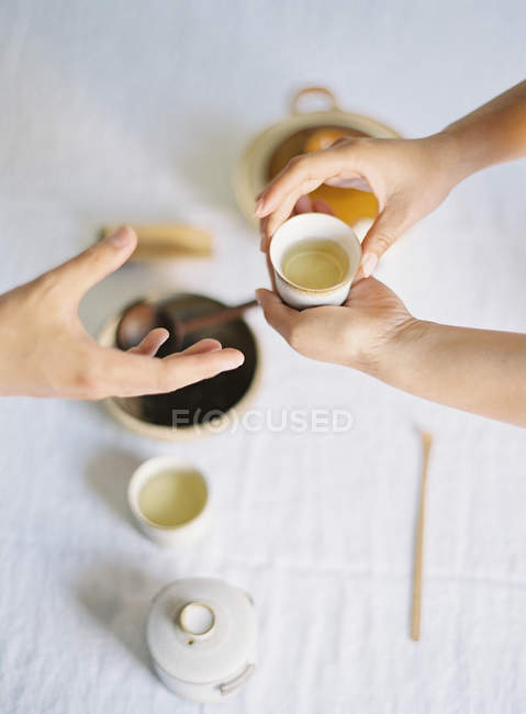 Hands passing cup of green tea — Stock Photo
