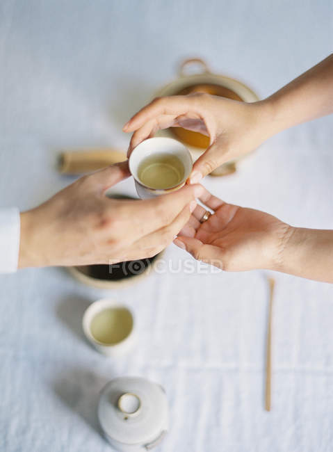 Hands holding tea cup during tea ceremony — Stock Photo
