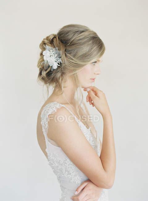 Mujer en vestido de novia con la mano a la barbilla - foto de stock