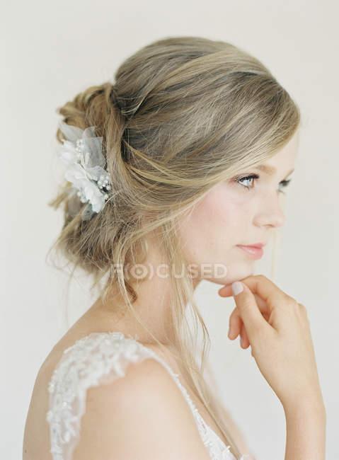 Женщине в свадебное платье с рукой подбородок — стоковое фото