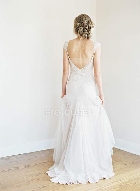 Femme en robe de mariée debout dans la chambre — Photo de stock