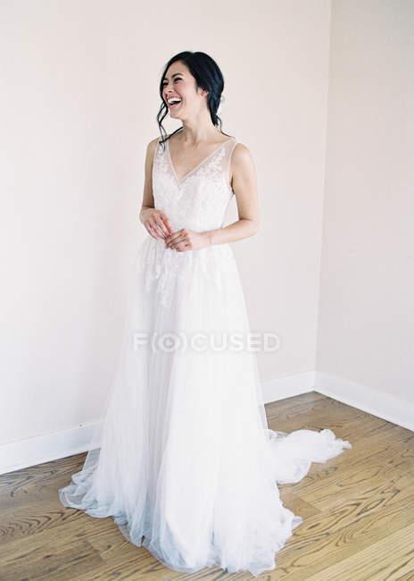 Frau im Brautkleid steht im Zimmer — Stockfoto