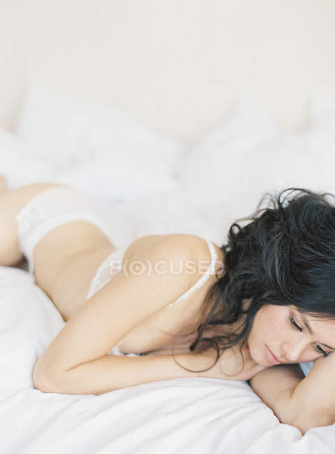 Woman in exquisite lingerie lying on bed — Stock Photo