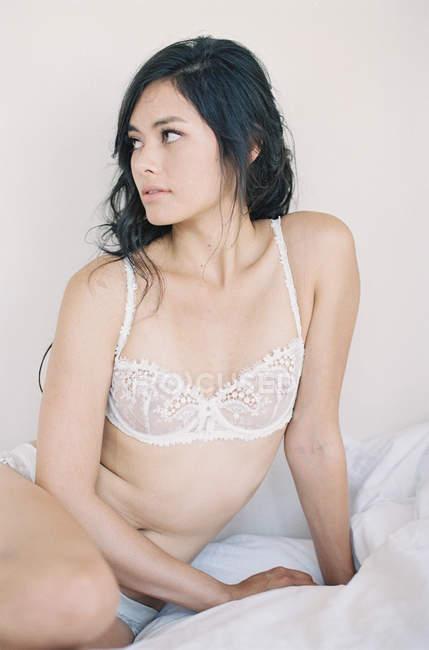Женщина в изысканное белье, сидя на кровати — стоковое фото