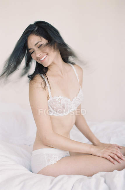 Woman in exquisite lingerie flipping hair — Stock Photo