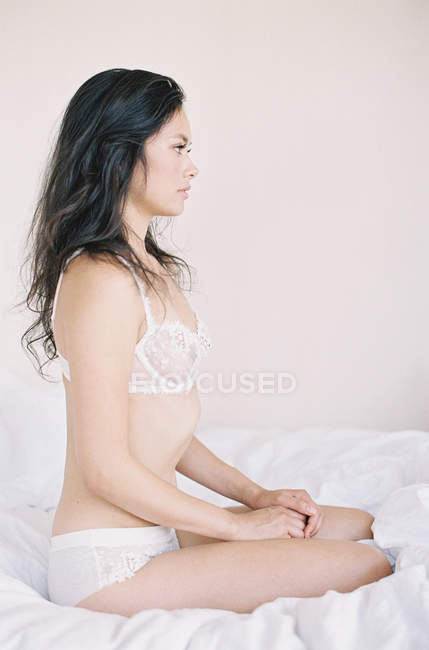 Woman in exquisite lingerie sitting on bed — Stock Photo