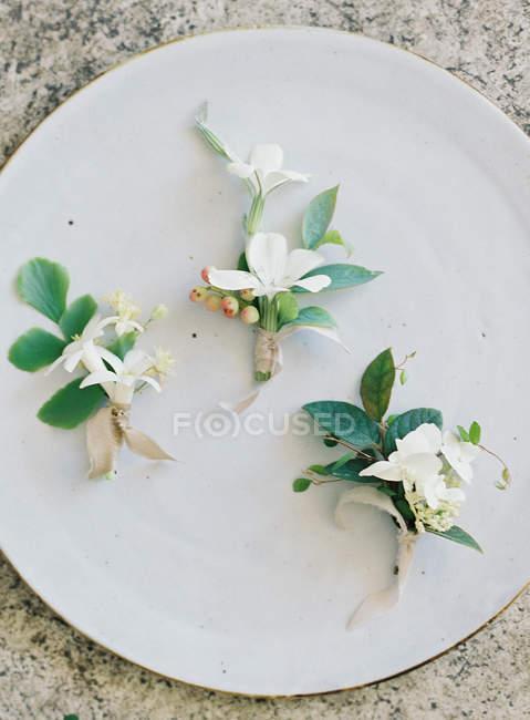 Wedding boutonnieres on white plate — Stock Photo